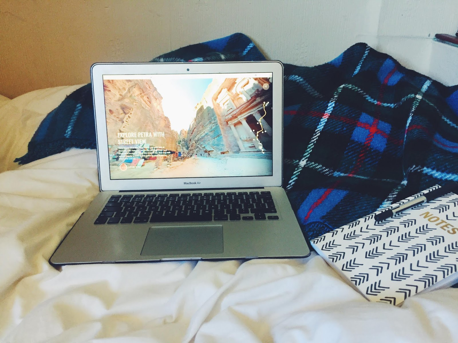 Laptop on bed with virtual tour of Petra archaeological site on screen