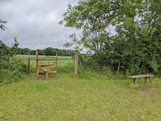 The stile and bench at the top of the hill - point 14