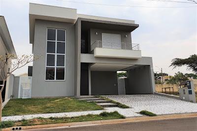 Os tons acinzentados combinam com o branco no acabamento externo da casa, com linhas limpas e volumetria destacada.