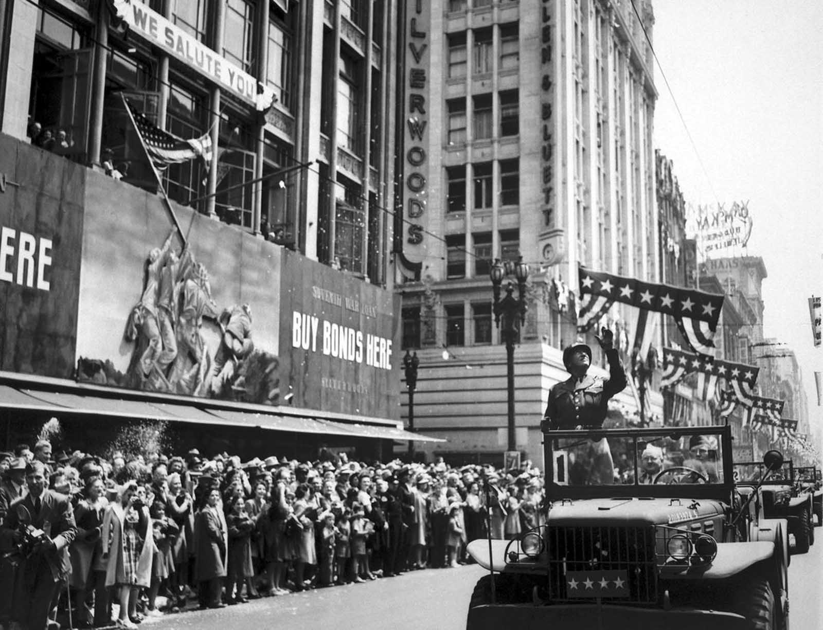 U.S. General George S. Patton acknowledges the cheers of thousands during a parade through downtown Los Angeles, California, on June 9, 1945. Shortly thereafter, Patton returned to Germany and controversy, as he advocated the employment of ex-Nazis in administrative positions in Bavaria; he was relieved of command of the 3rd Army and died of injuries from a traffic accident in December, after his return home. Joe Rosenthal's famous Iwo Jima flag-raising photograph is visible on the war bonds billboard.