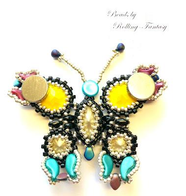 Aus Perlen gefädelter Schmetterling in gelb, blau, rot und schwarz - Rückseinte