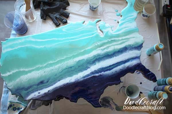 Using the blowdryer to blow the resin for an Ocean Resin Pour on USA Cutout DIY tutorial to make home decor look like the waves of the ocean in ombre shades of blue.