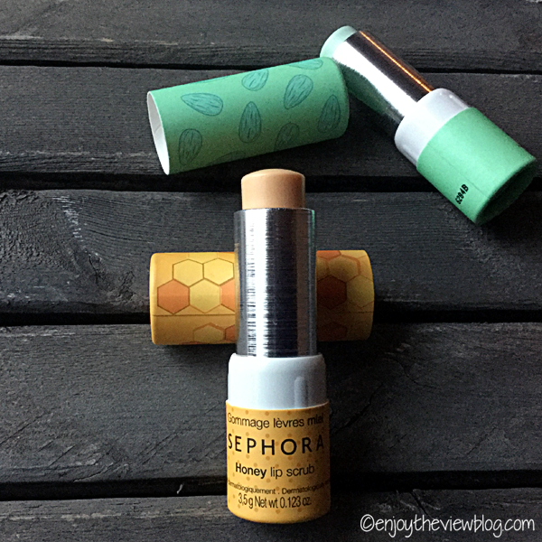 An open tube of Sephora Honey Lip Scrub lying on a wooden table with a tube of Sephora Almond Lip Balm in the background