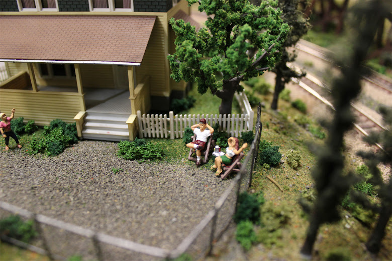 Two model figures lounge in lawn chairs in front of a Kate's Colonial Home kit