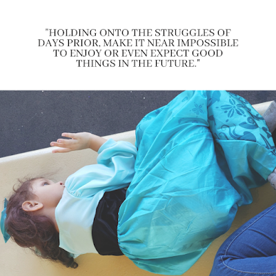 A little curly-haired girl in a blue dress, lying down on a bench.