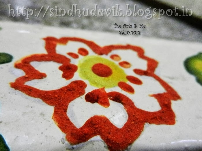 A freehand floral rangoli made of herbal products: sigate powder, vermilion and turmeric
