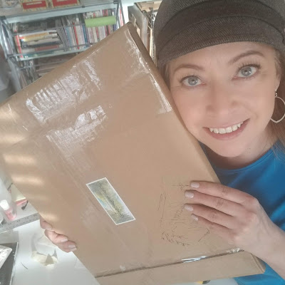 Newest art sale ready to ship!  Brown cardboard package in my hands.