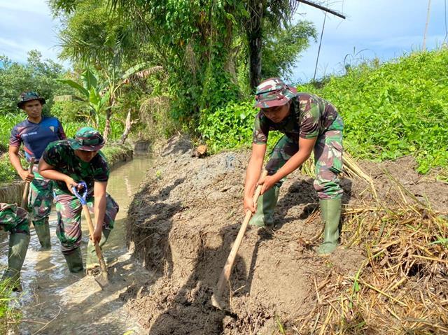 Personel Satgas TMMD Kodim 0207/Simalungun Bersama Masyarakat Bersihkan Saluran Irigasi Kesawah
