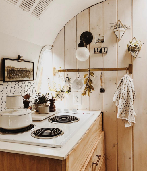 natural wood, honeycomb backsplash tile pattern, and a lot of plants filled this tiny kitchen vintage airstream