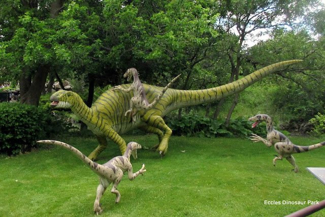 colorful statues depicting small dinosaurs attacking in a pack