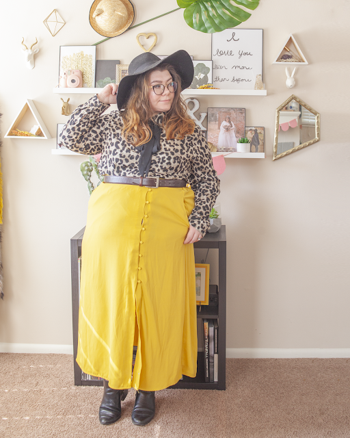An outfit consisting of a black wide brim hat, an animal print blouse with an attached black ribbon tied into a bow, tucked into a yellow button down skirt and black Chelsea boots.