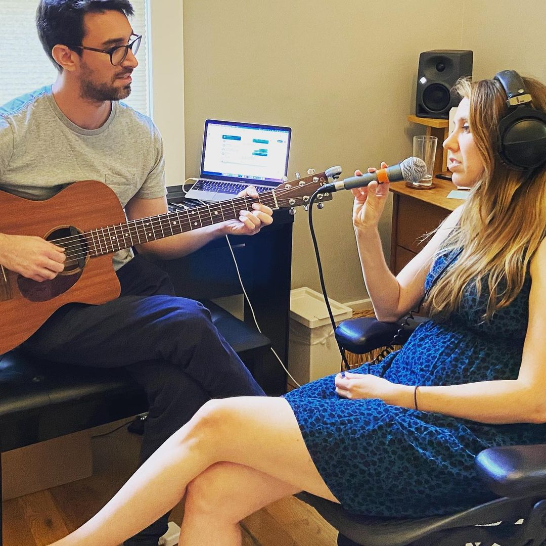 Suzie holding a microphone and wearing headphones at her side Jesse holding the acoustic guitar