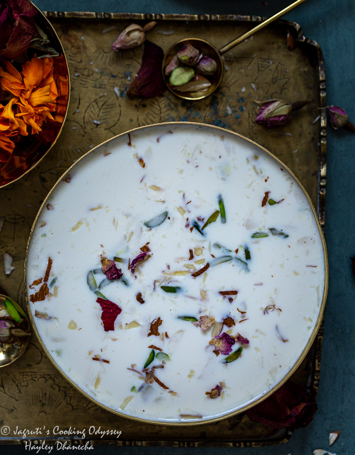 Closeup shot of served basundi in a bowl next to a spoon on a tray.