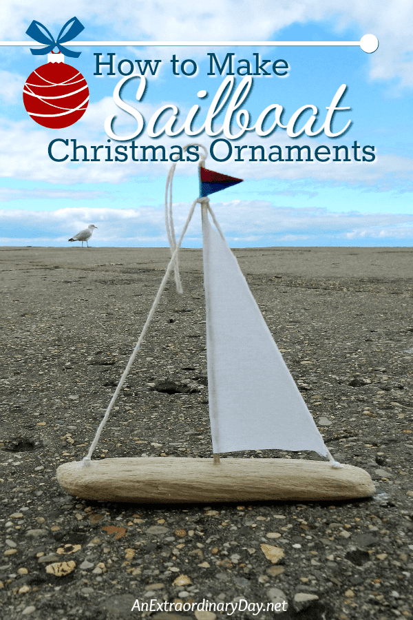 Driftwood and fabric little sailboat ornament on the beach