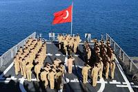 Denizdeki bir Türk savaş gemisinin arka güvertesinde Türk bayrağı önünde selam durmuş olan gemi mürettebatı