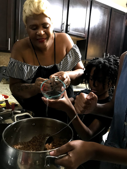 Image:Mom helping daughter pour water into the food for simmering