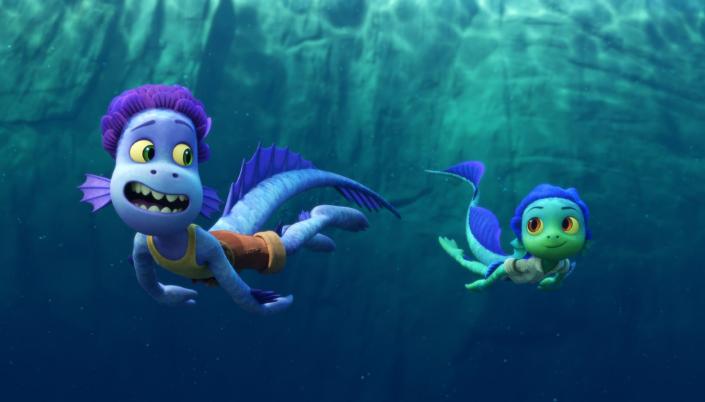 Imagem: Luca e Alberto estão nadando e sorrindo no fundo do mar. Eles são seres aquaticos e humanoides com calda. Possuem escamas, as de alberto são azuis e roxas e as de luca são verde e azul. Os dois usam roupa de humanos, camisa regata e bermuda.