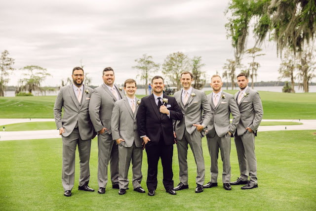 groom in black tux and groomsmen in grey suits