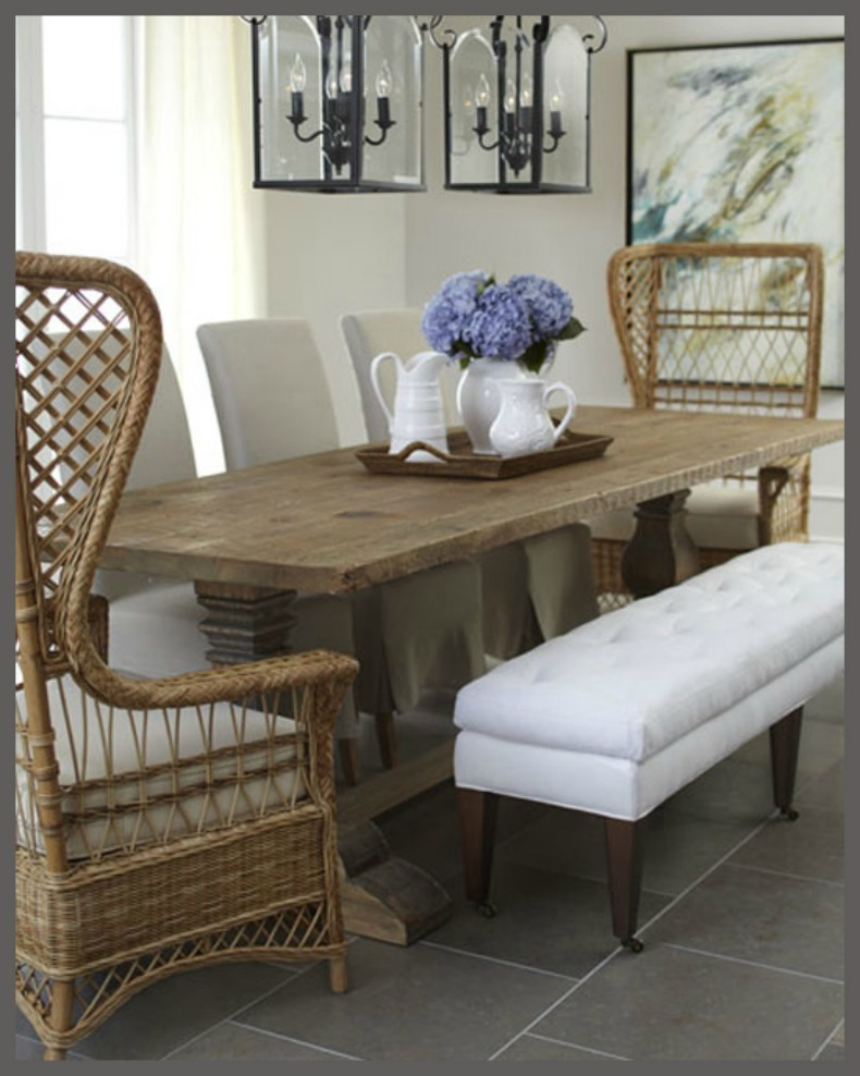 Coastal dining room with wicker wing chairs, white upholstered bench and white slipcover chairs