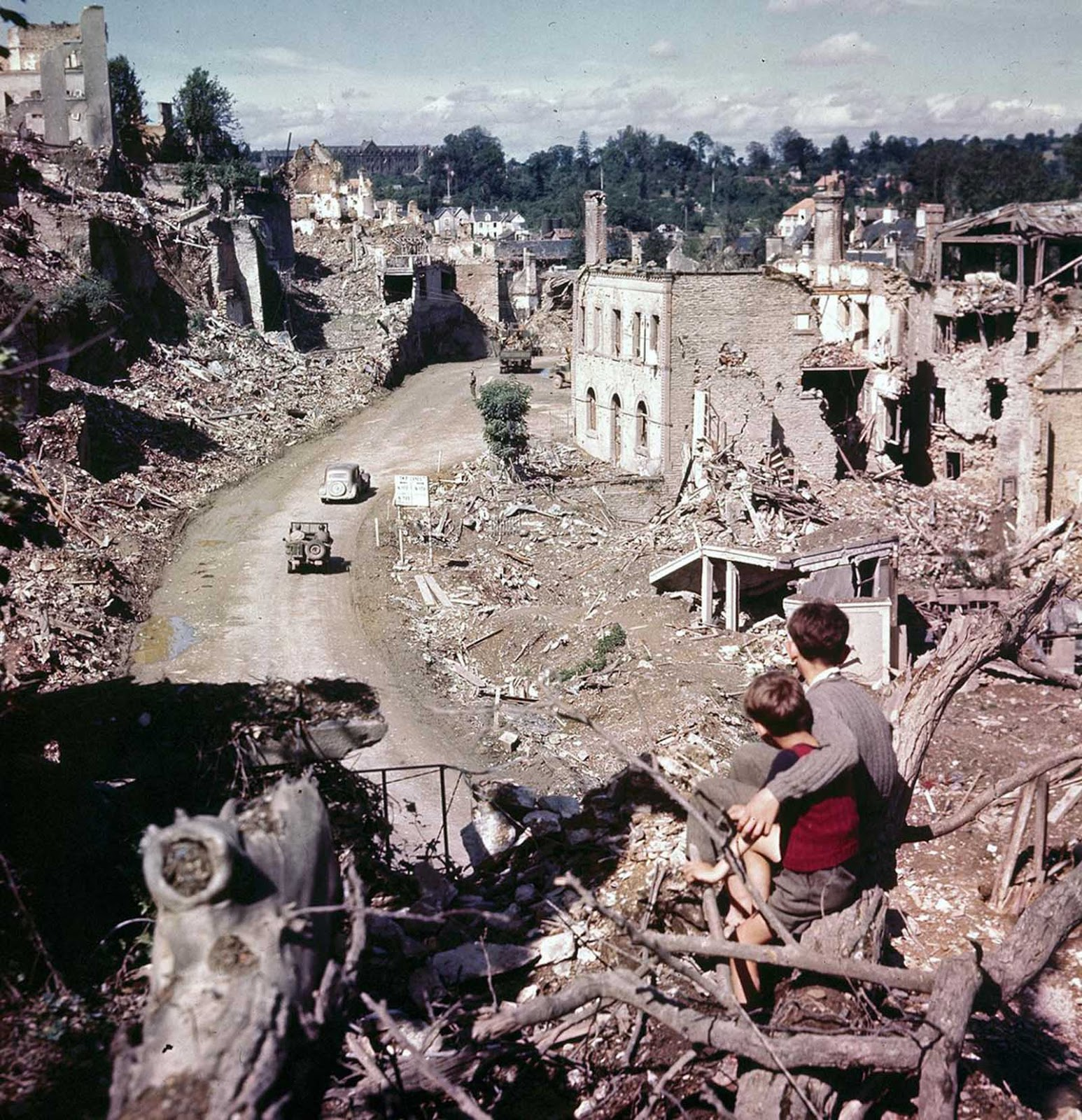 A view from a hilltop overlooking the road leading into St. Lo in July of 1944. Two French children in the foreground watch convoys and trucks of equipment go through their almost completely destroyed city en route to the front.