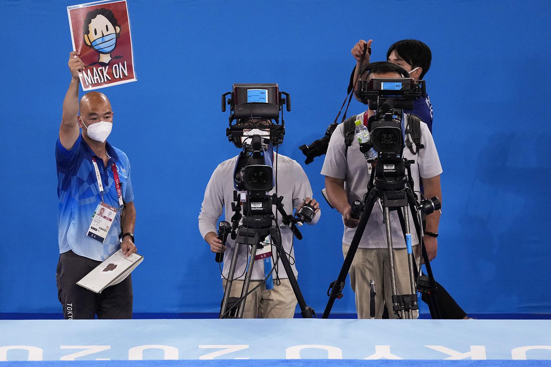 Rich Lam, trái, người quản lý hình ảnh môn thể dục dụng cụ, giơ tấm biển báo hiệu các vận động viên đeo khẩu trang khi đứng trên bục nhận huy chương sau cuộc thi thể dục nghệ thuật đồng đội nam tại Thế vận hội mùa hè 2020. Ảnh chụp vào ngày 26 tháng 7 năm 2021, tại Tokyo, Nhật Bản của Ashley Landis/AP.