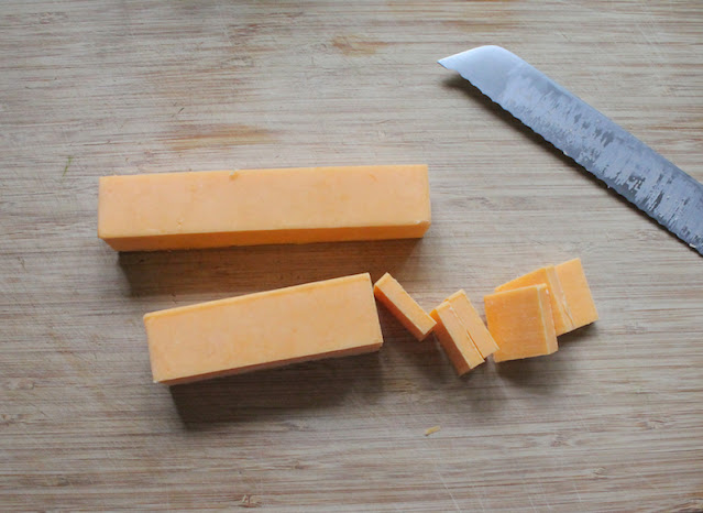 Slicing the cheddar cheese for making spicy marinated cheese.