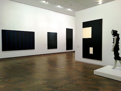 Interior view of an exhibition of black art, with several black work on display to the left, and a black Issey Miyake dress on display on a  mannequin on the right.