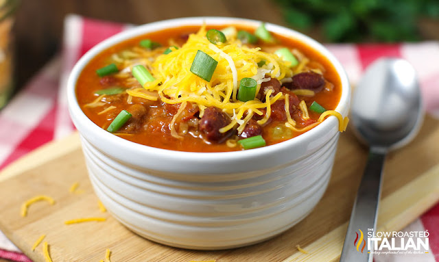 homemade version of Wendys chilli topped with shredded cheese and scallions in white bowl