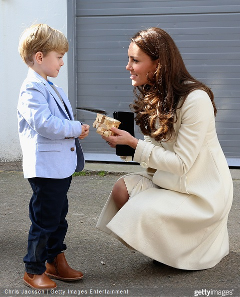 Catherine, Duchess of Cambridge is presented with a train for Prince George by actor Oliver Barker during an official visit to the set of Downton Abbey