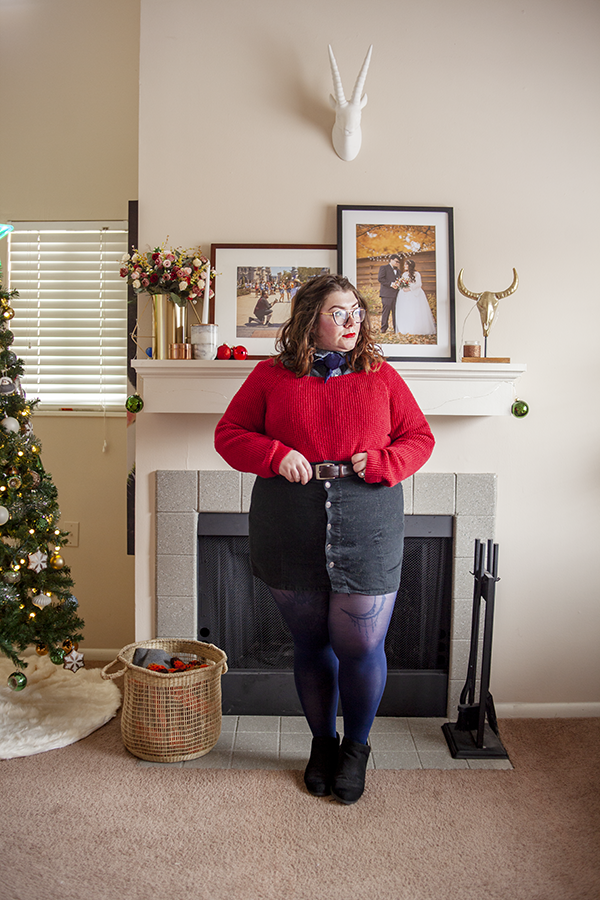 An outfit consisting of chambray button down under a red sweater tucked into a black button down miniskirt and black ankle boots.