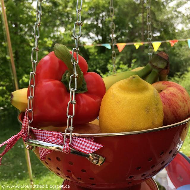 Paprika, Zitrone, Äpfel und Bananen in rotem Sieb aus Emaille