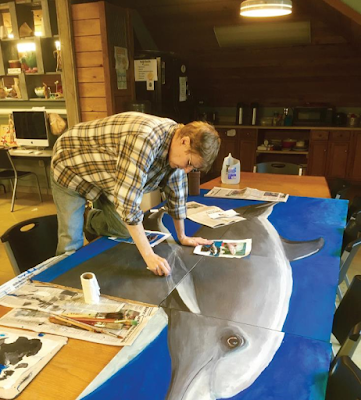 Artist working on large painting of dolphin