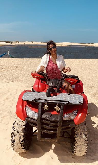 mulher morena, jovem, cabelo preto, oculos escuros, blusa rosa e blaser branco em um quadriciclo vermelho proximo a um oasis