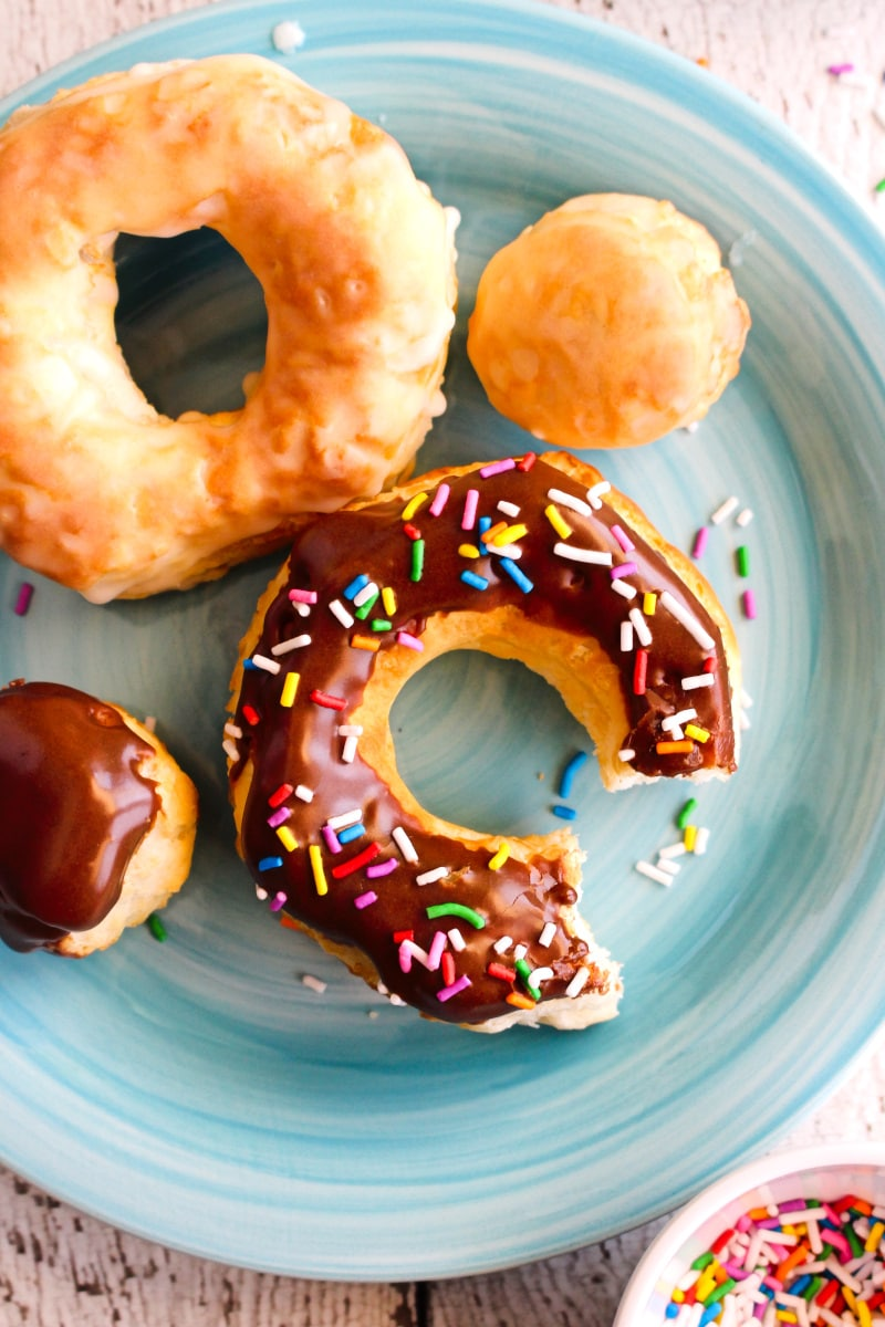 A whole glazed donut and a chocolate dipped donuts with rainbow sprinkles that has a bite taken out of it on a blue plate.