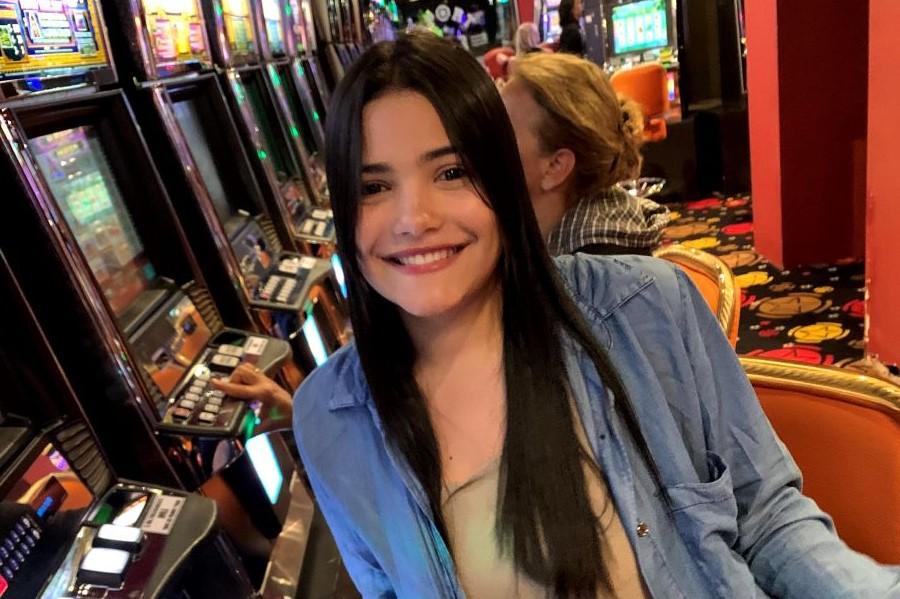 mulher jovem de cabelo preto, pele branca, short jeans, e blusa marrom clara e camiseta longa azul, sentada em um cassino