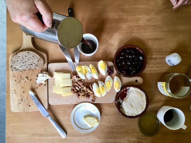 Draufsicht: Frühstückstisch mit Brot, Käse, Ei, Oliven und Kaffee