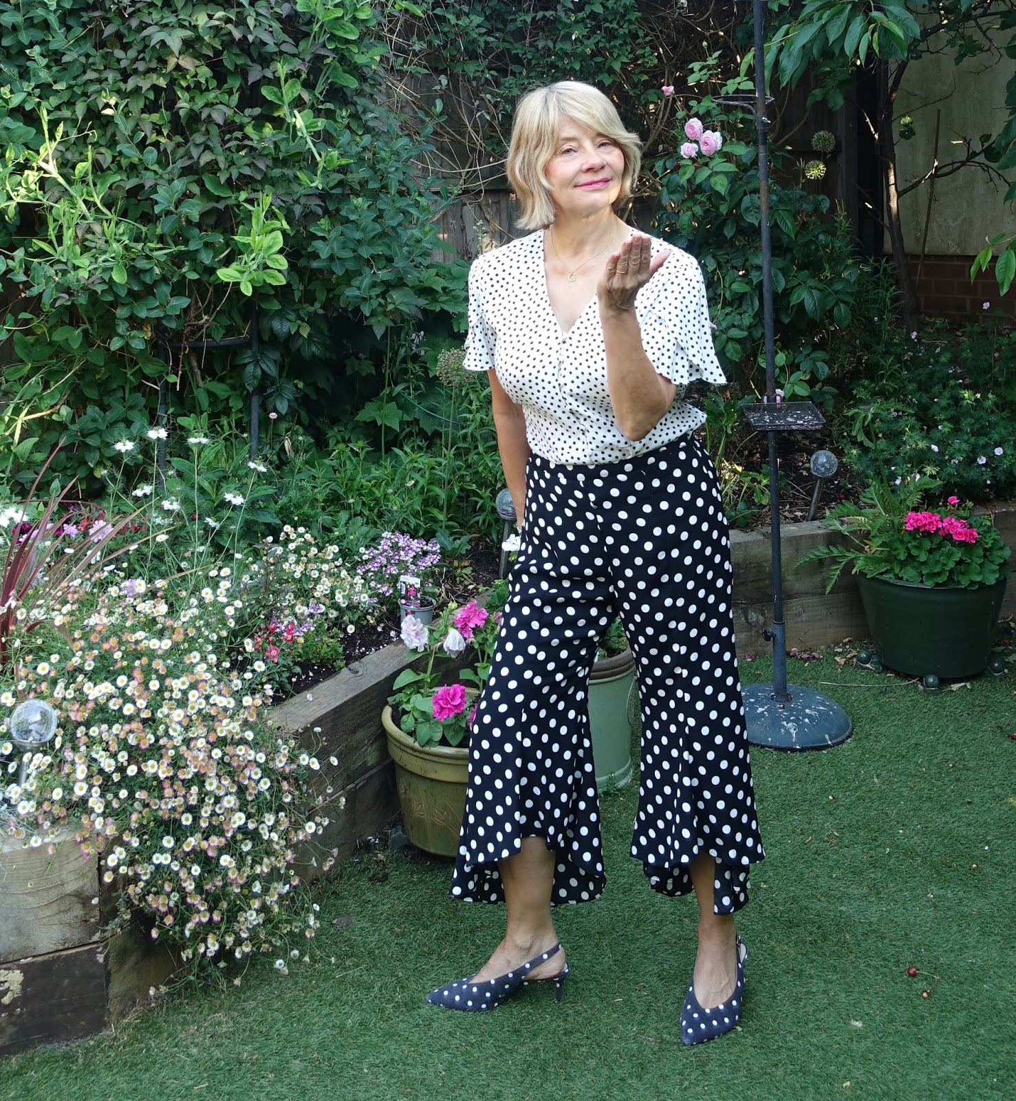 Garden shot of over-50s style blogger Gail Hanlon in polka dot frilled bottom trousers, polka dot top and polka dot sling back shoes