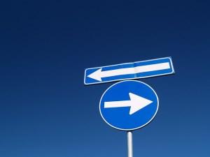 A imagem mostra dois sinais de estrada, apontando em sentidos opostos.