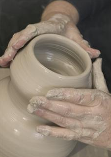 photo of a potter's hands forming wet clay into a pot