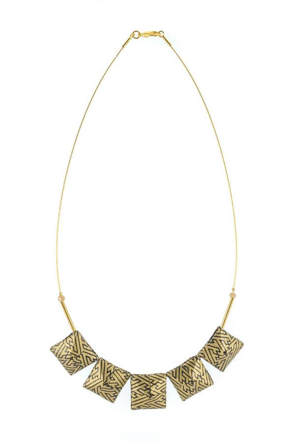 five folded paper squares in geometric black and gold pattern strung on golden necklace wire