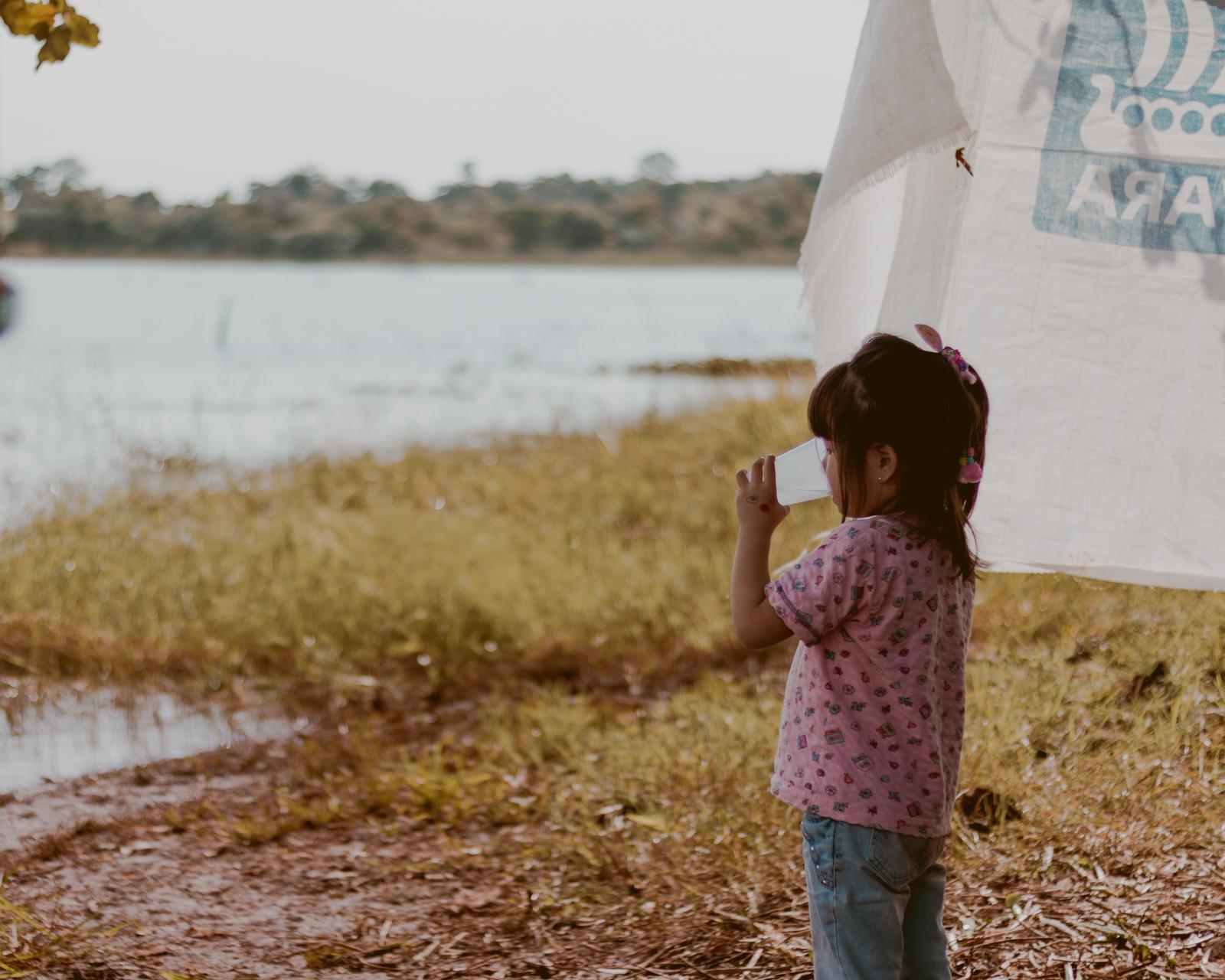 criança bebendo água no acampamento