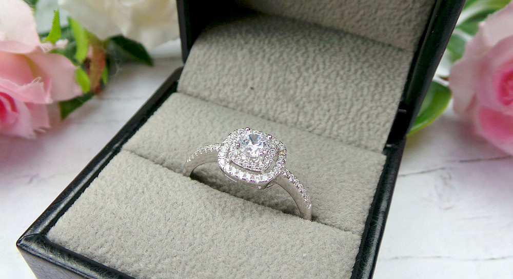 A square diamond ring with 3 layers in a box with blurred roses in the background
