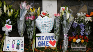 Tributes pour in as signs and flowers are placed at a Memorial