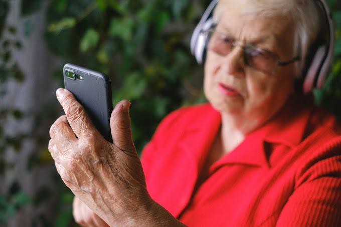 Mulher idosa usando headphone e olhando para a tela do celular. Ela tem cabelos brancos, usa blusa vermelha e usa óculos de grau com lentes avermelhadas