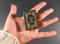A hand holding a miniature, gold stamped book.