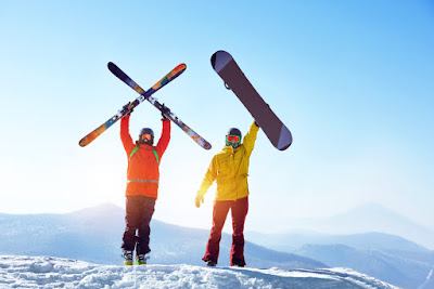 Pareja de esquiador y de snowboard en la cima de las colinas de Dalvik