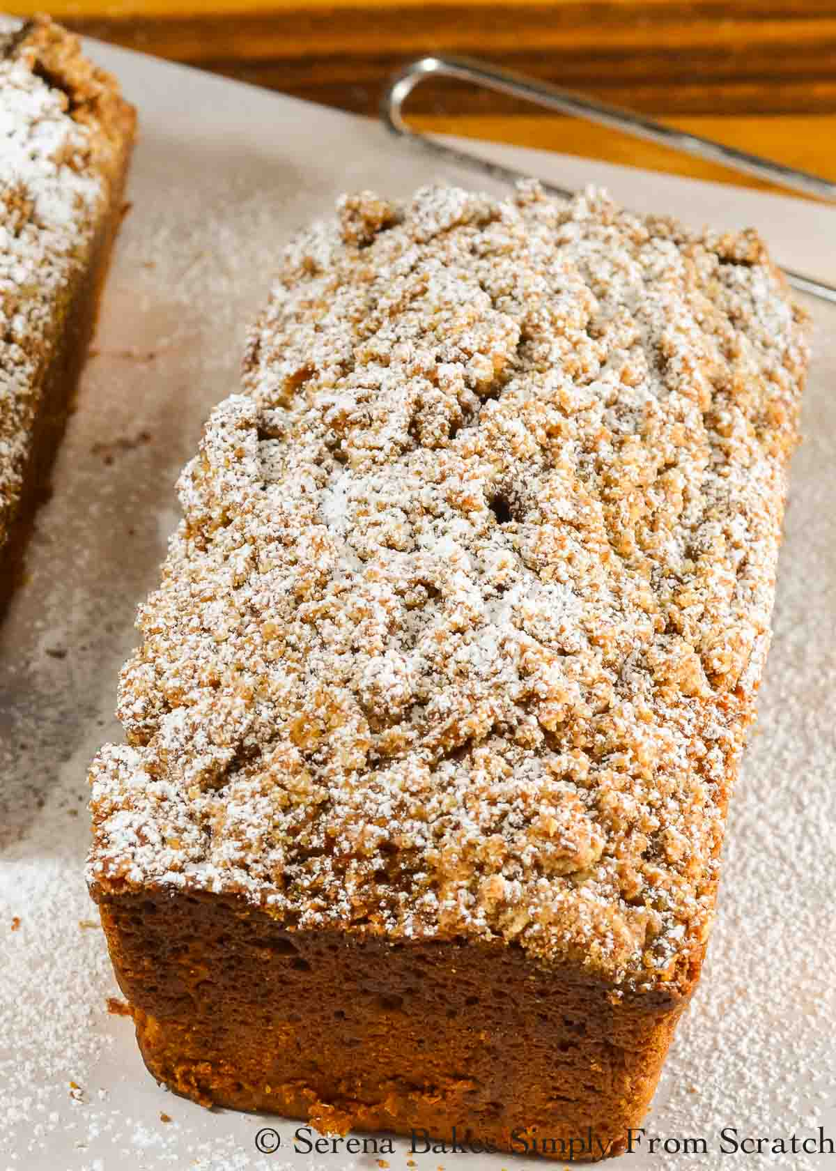 Pumpkin Bread with Streusel lightly dusted with powdered sugar on a piece of parchment paper.