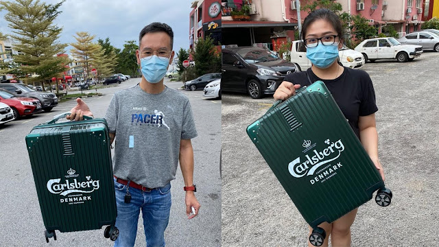 "Ms. Lim Ann Huei (林安卉) and Mr. Lee Hock Mun (李协满) were delighted to redeem their emerald green 20"" Carlsberg luggage bags from their supermarket purchases."