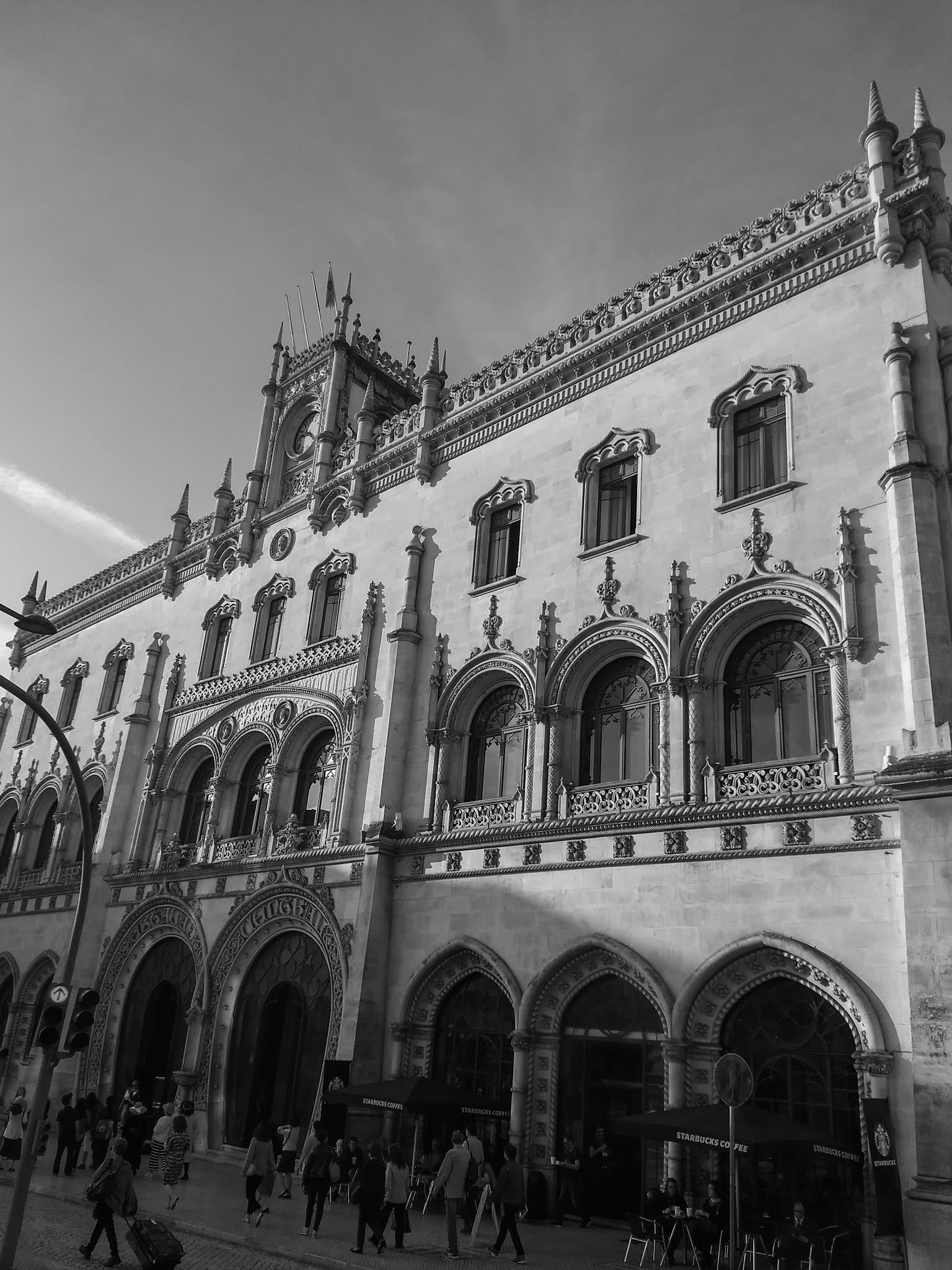 Black and white photo of Rossio Railway Station building on the outside in Lisbon, Portugal.