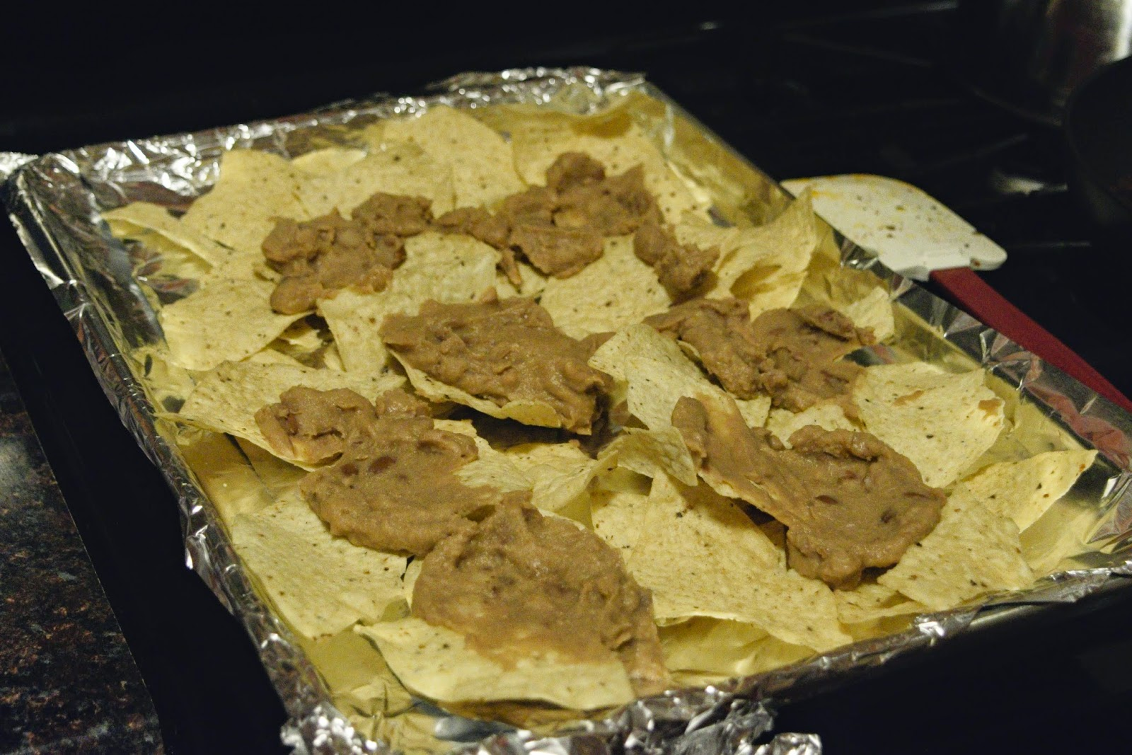 The refried beans being added to the tortilla chips for the nachos supreme recipe.